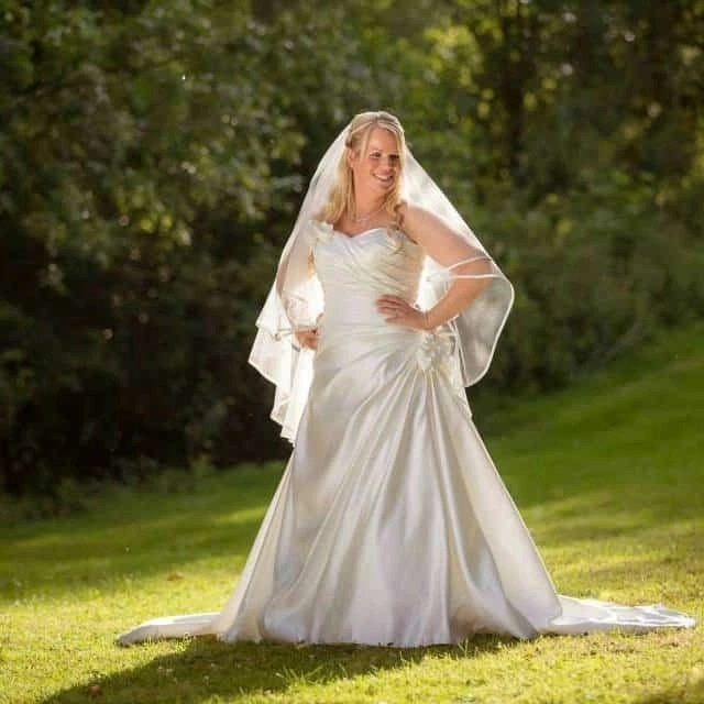 Two tier fingertip length veil with a satin edge on real bride Emily wearing satin wedding dress