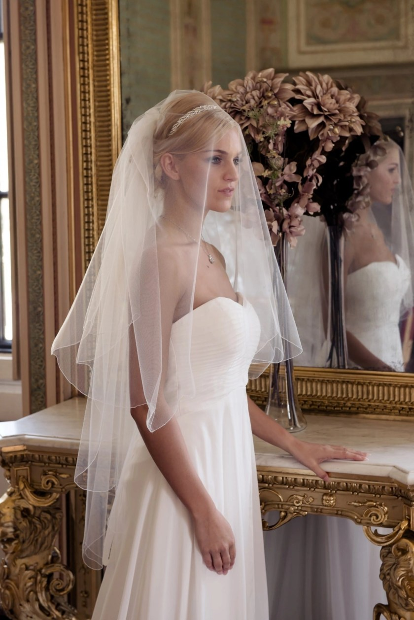 Bride in grand golden ballroom wearing a wedding veil over the face