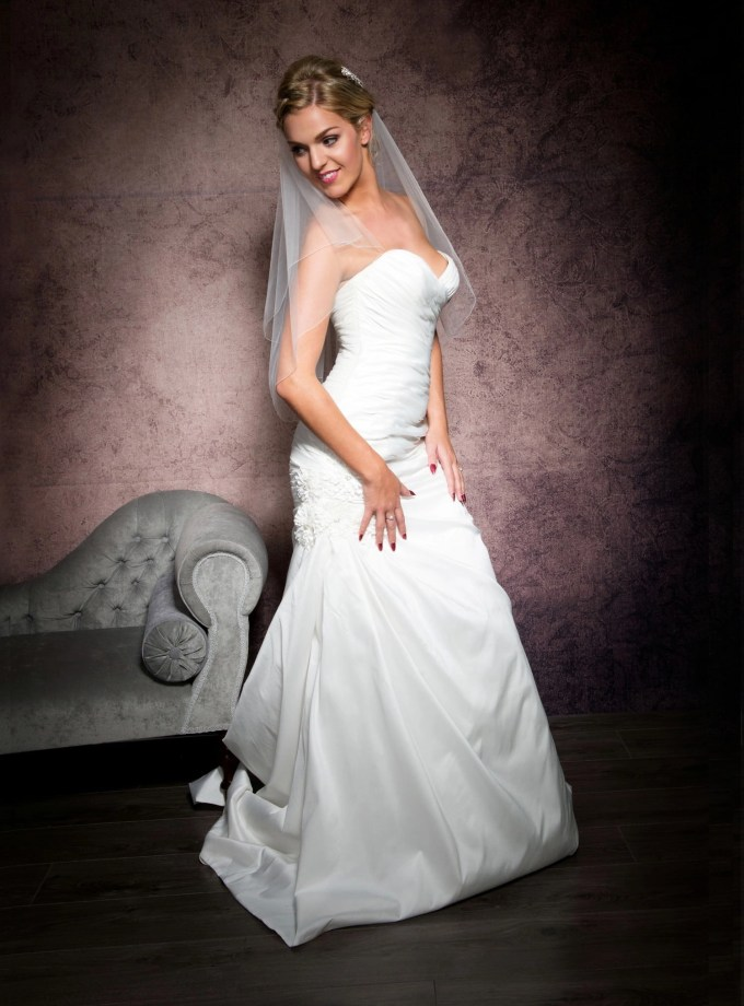 Happy bride wearing a simple waist length veil