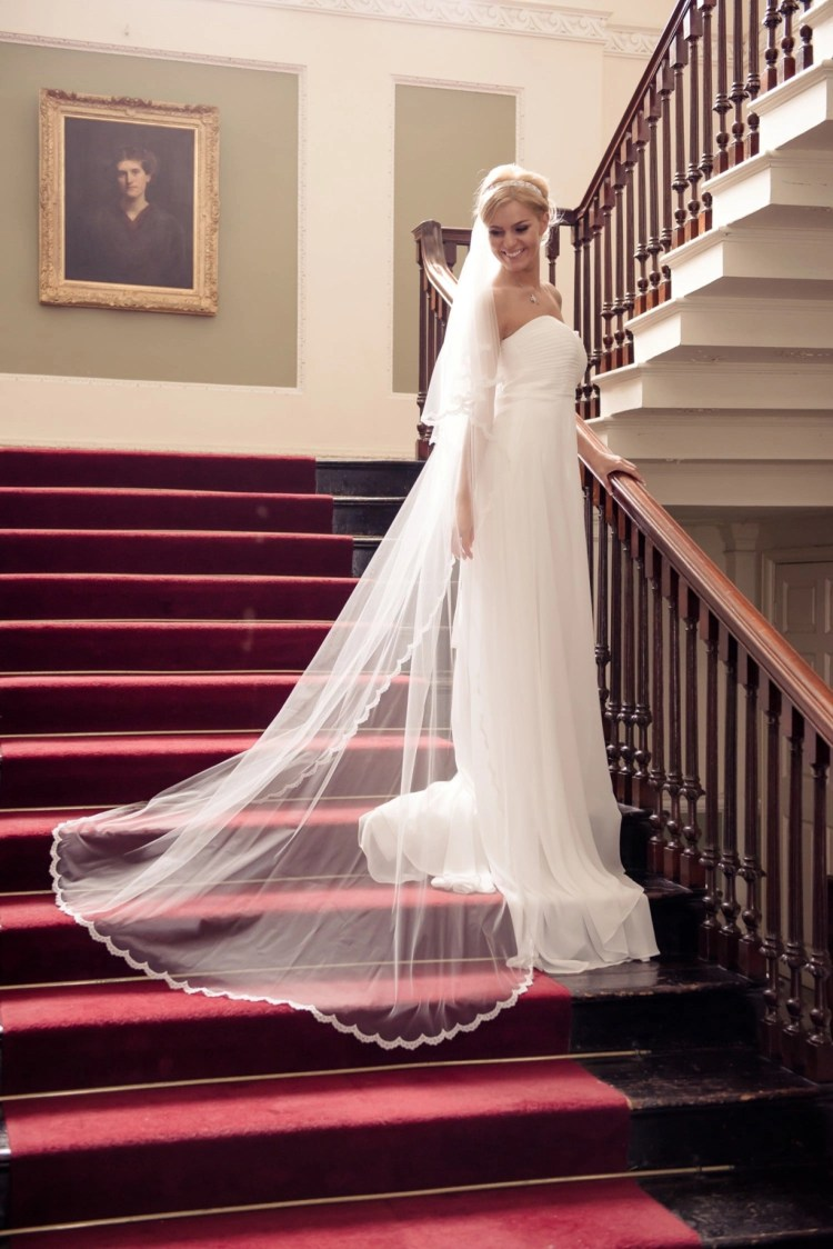 Bride on grand staircase wearing long flowing veil with a narrow lace edge