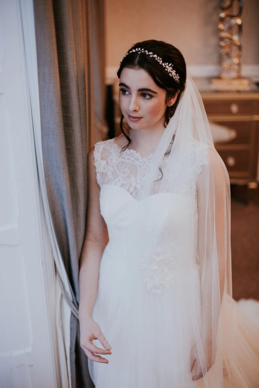 Bride looking out a window wearing wedding dress and veil in Silk Effect tulle