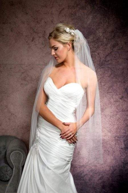 Demure bride with clasped hands wearing veil with a satin edge
