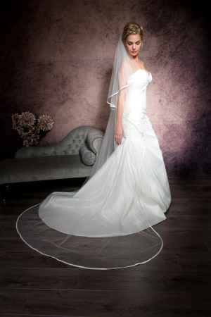 Bride wearing a long flowing chapel length veil with satin edges