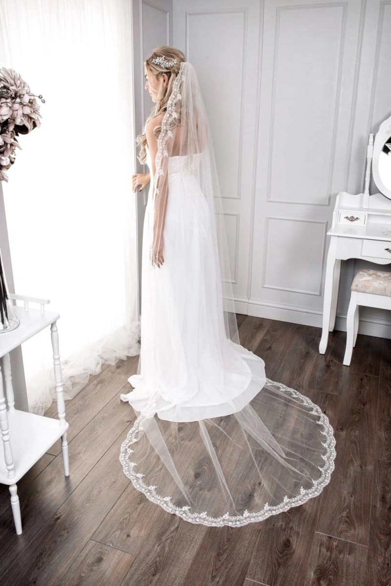 Bride at window wearing single layer chapel length veil with full lace edge