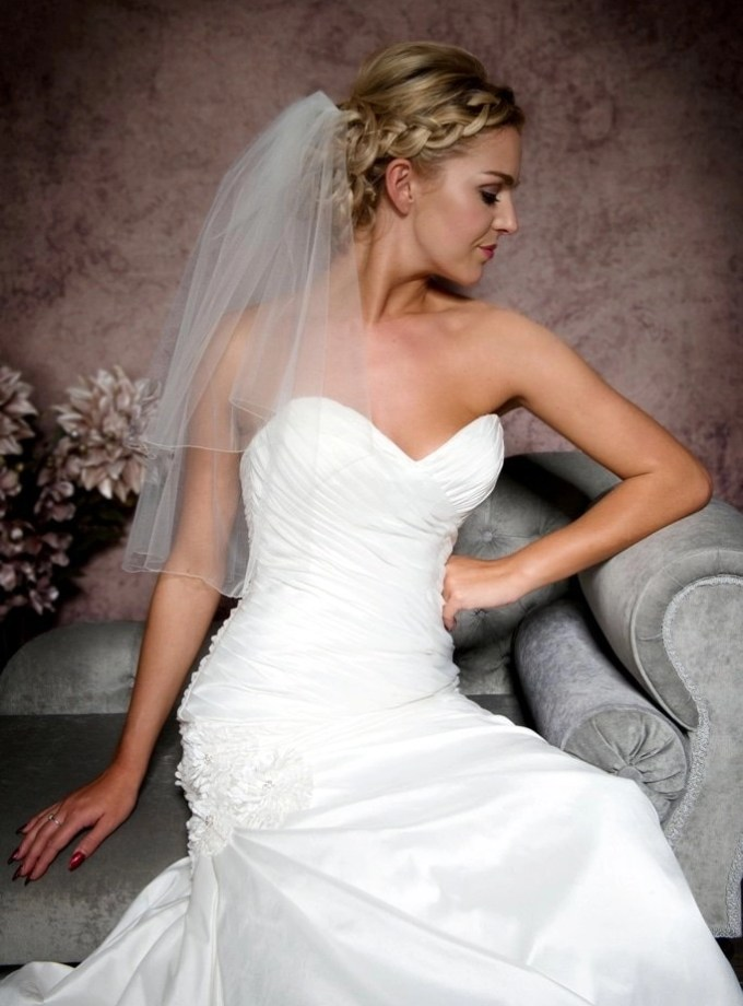 Close up of bride sitting on chaise wearing an elbow length pencil edge veil