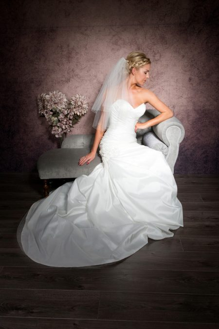 Bride sitting on chaise wearing an elbow length pencil edge veil