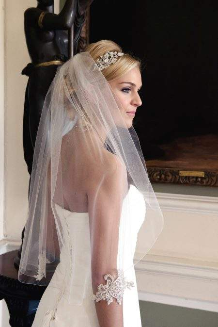 Bride wearing waist length single layer veil with silver lace