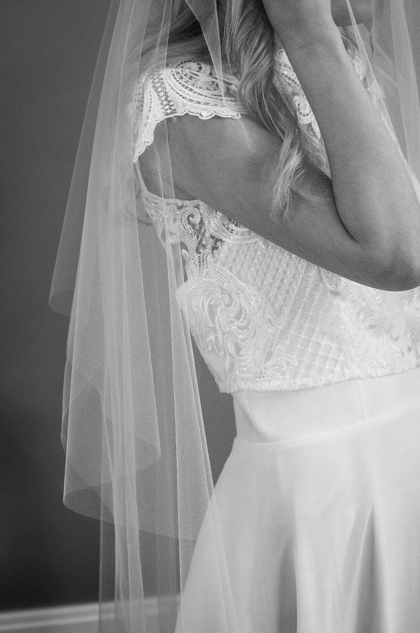 Angelina - two layer plain wedding veil with a hand cut edge in waltz length closeup side view bw