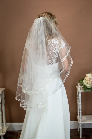Candice - short two tier hip length veil with a satin and organza ribbon edge on a bride