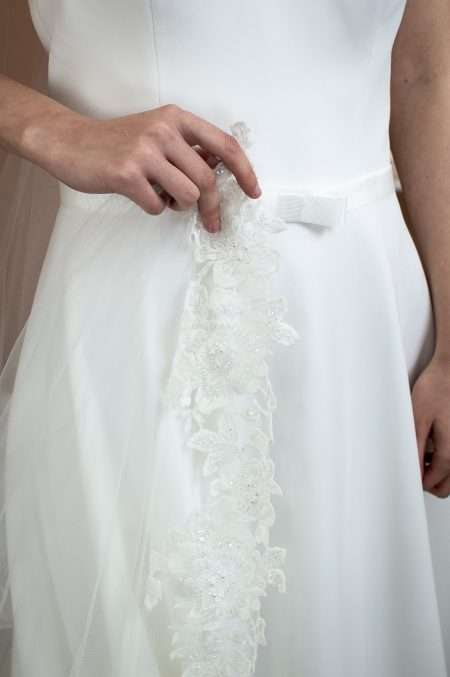 Celeste - one layer chapel length veil with a floral lace bottom on bride holding the lace