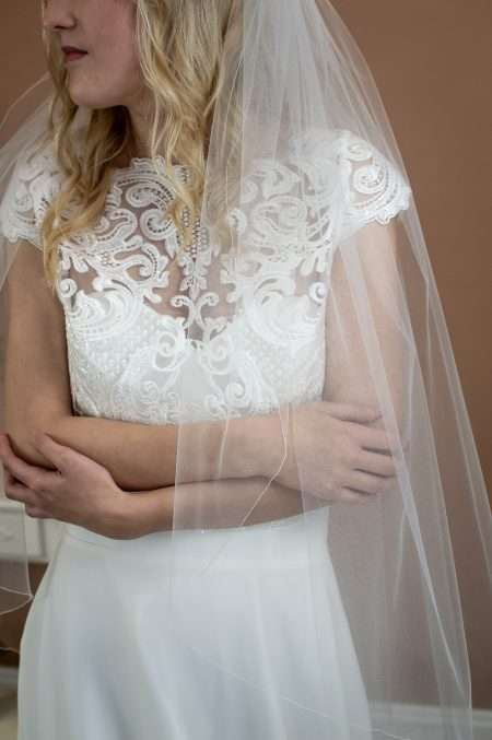 Erica - single layer hip length veil with a simple edge front view closeup