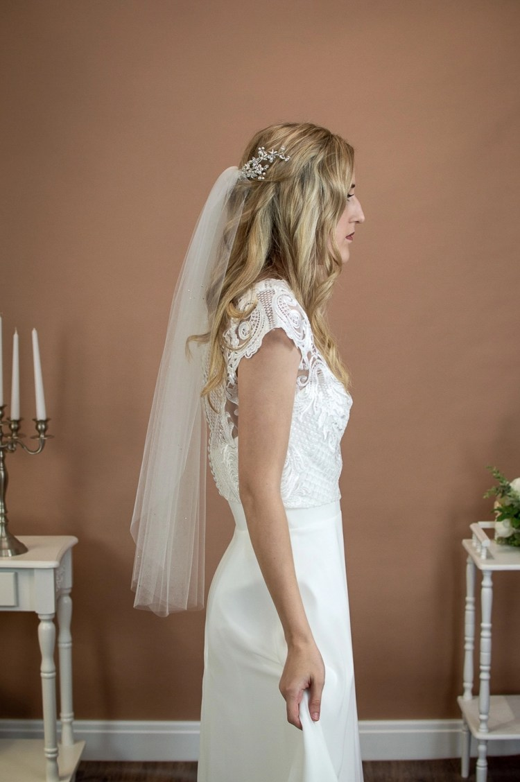 Evie - one layer short waist length wedding veil with a cut edge and scattered diamantes on a bride