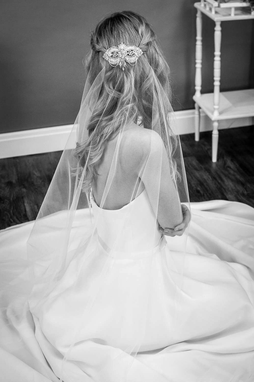 Gloria - one layer chapel length barely there veil with a crystal beaded veil topper bride sitting down bw