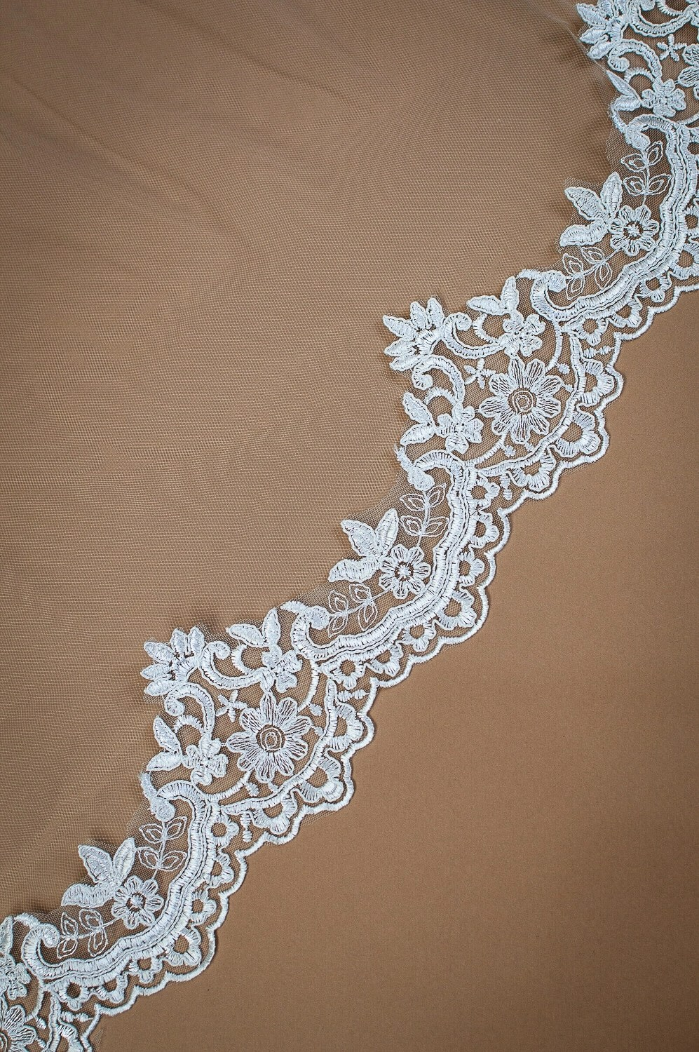 Harmony - single layer chapel length lace edged mantilla veil with comb closeup on solid background