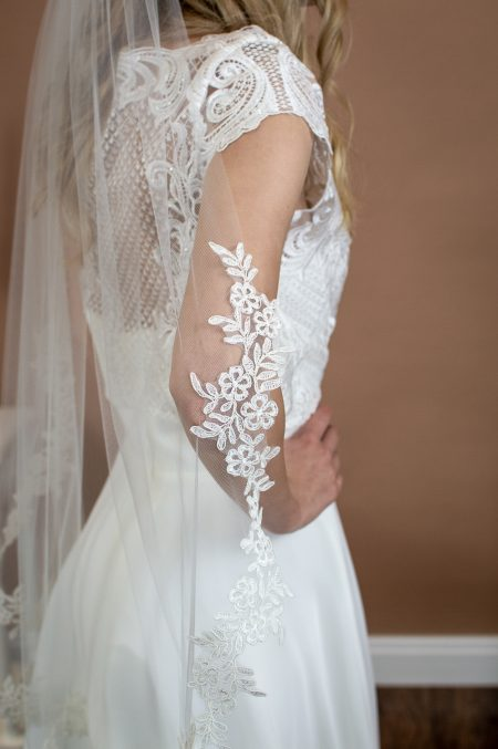 Heather - single layer hip length veil with a wavy lace applique edge side closeup