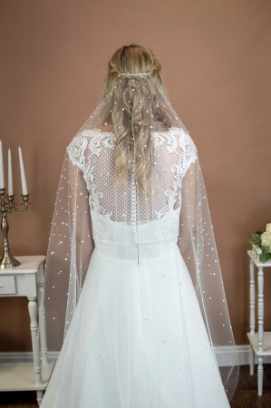 Violet - Single layer short barely there veil in fingertip length with a cut edge and mixed size pearls on a bride