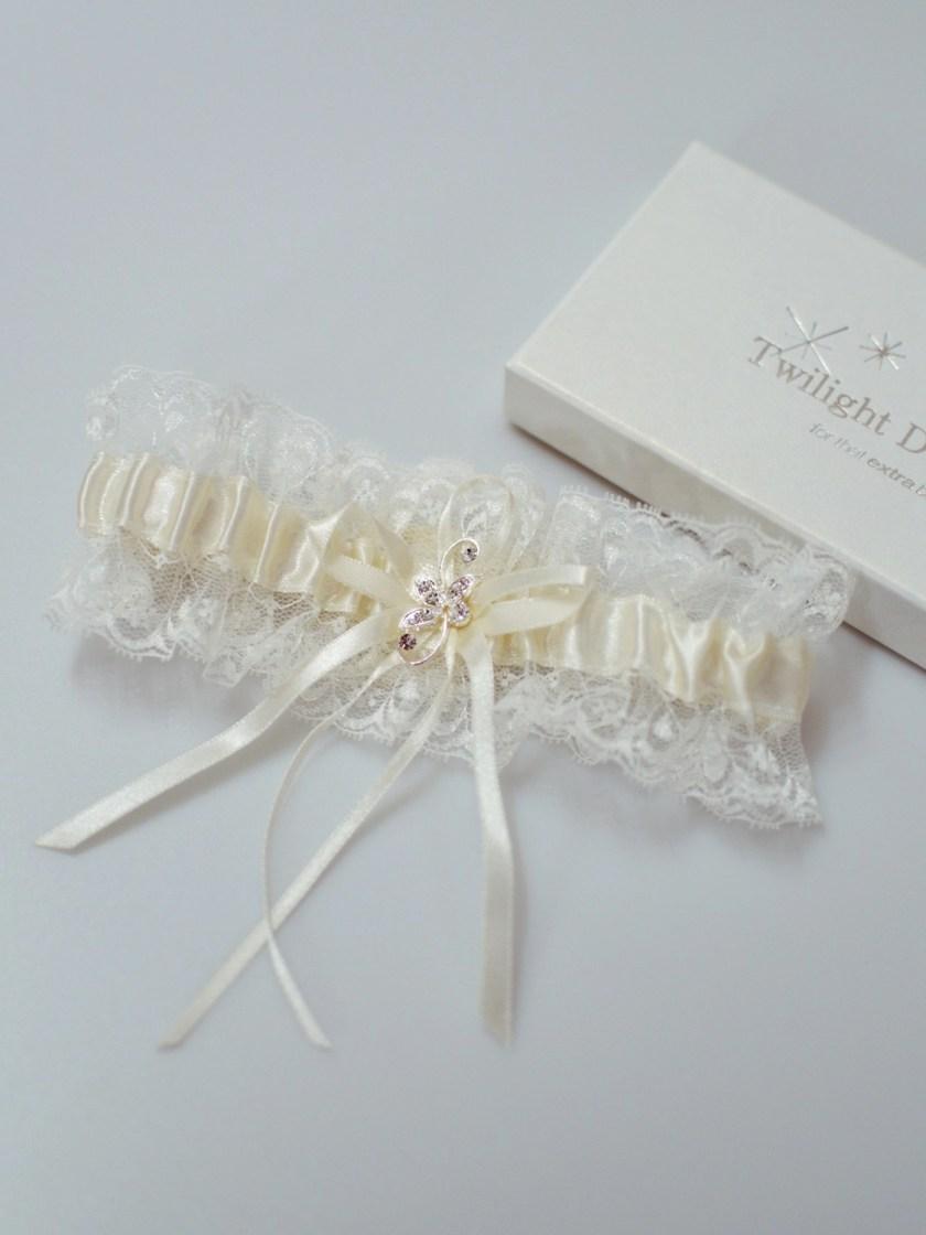 Pretty ivory wedding garter with diamante brooch detail flatlay TLG511