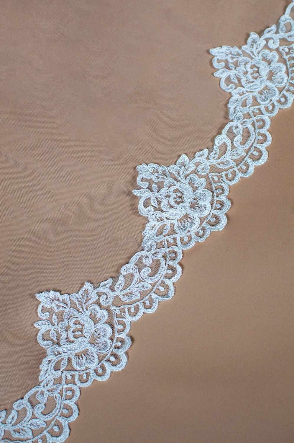 Astrid lace edging for wedding veil on solid background closeup