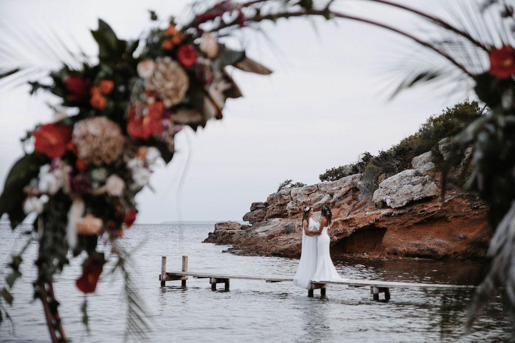 Two brides on jetty destination gay wedding, lesbian brides