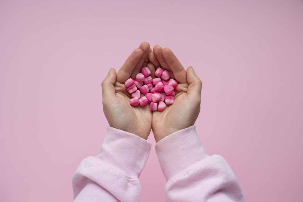 person holding pink candies in form in hearts in hands