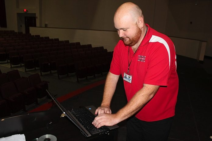 Working on the computer is the largest part in teaching high school band for Hernandez