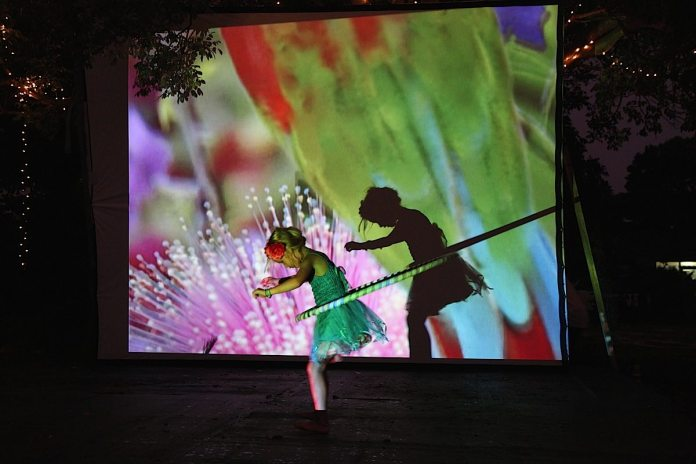 A young hooper casts a shadow double on the canvas of Nicholas Bergery's 'Dream Projections' at a previous Midsummer's Night Dream & Spectacle.