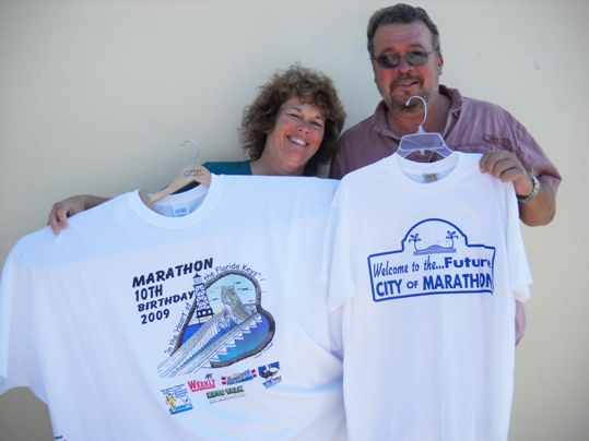 Marathon Mayor Ginger Snead and Marathon Vice Mayor Mike Cinque pose with two of Marathon's greatest tshirt. Snead holds the 10th Anniversary shirt designed by Gary Clark. Cinque is with the incorporation shirt from ten years ago