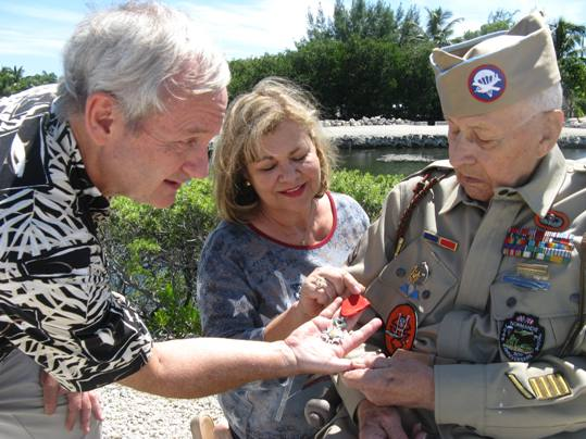 D-Day paratrooper Howard Huebner shows his French Legion of Honor badge to his daughter, Pam Steadman, and local filmmaker Richard Warner. The medal is the highest honor bestowed by the French government and the subject of Warner's new film