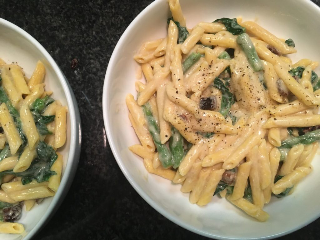 goat cheese alfredo sauce and pasta with sundried tomatoes, asparagus and spinach