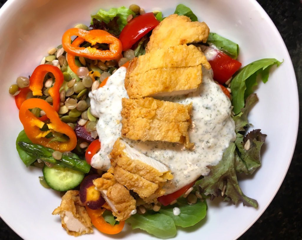Healthier version of fried chicken on a salad with veggies and lots of dietary fiber.  The dressing is made from goat's milk yogurt and Ranch seasonings.