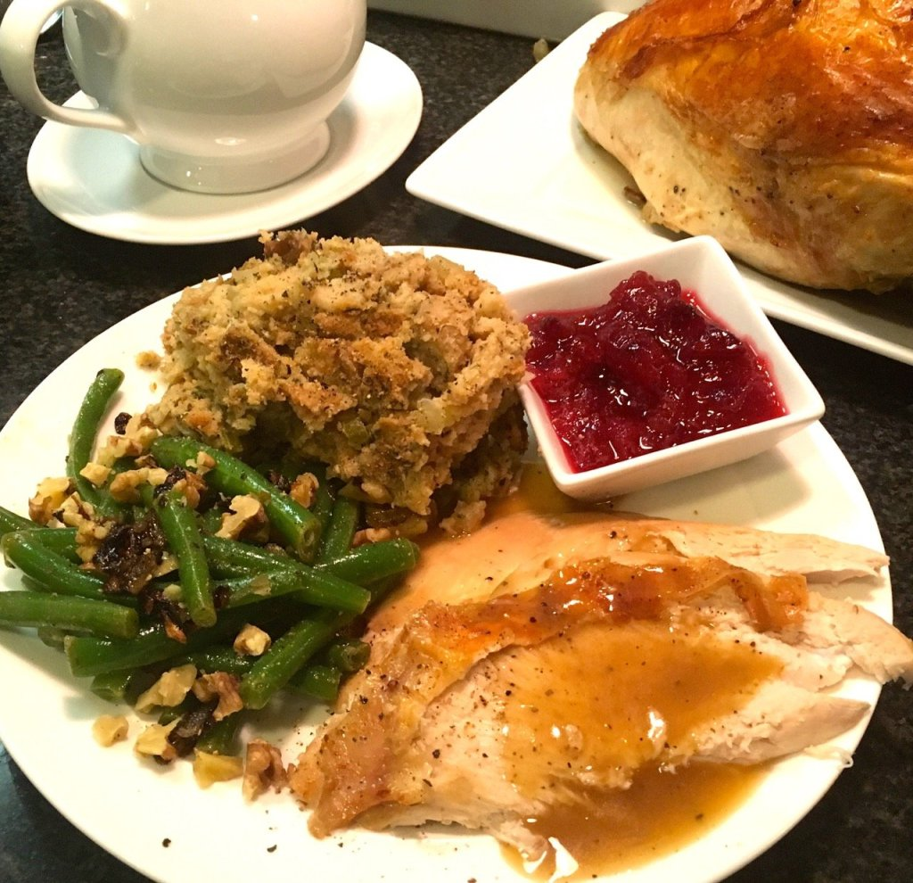 Thanksgiving dinner with perfect roasted turkey, gluten-free stuffing, cranberry sauce and fancy green beans.