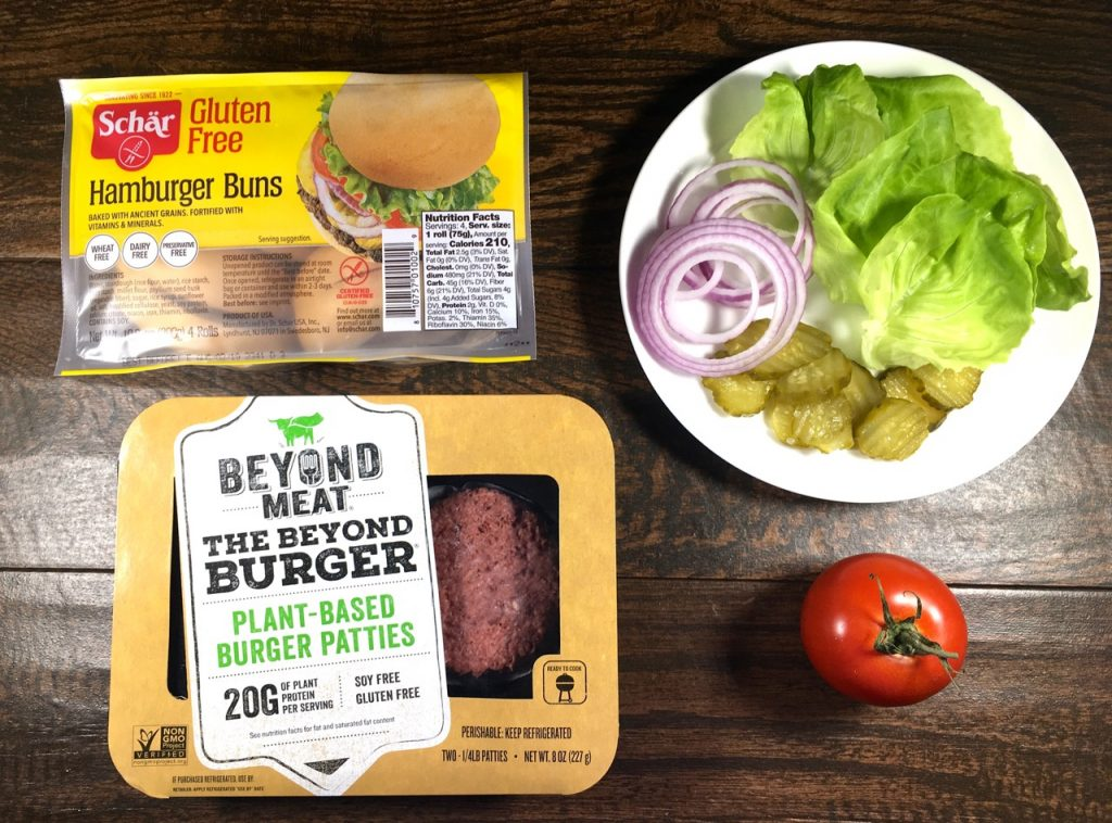 gluten-free Beyond Meat plant-based burger patties on Schär gluten-free hamburger buns with lettuce, onions, pickles and tomato