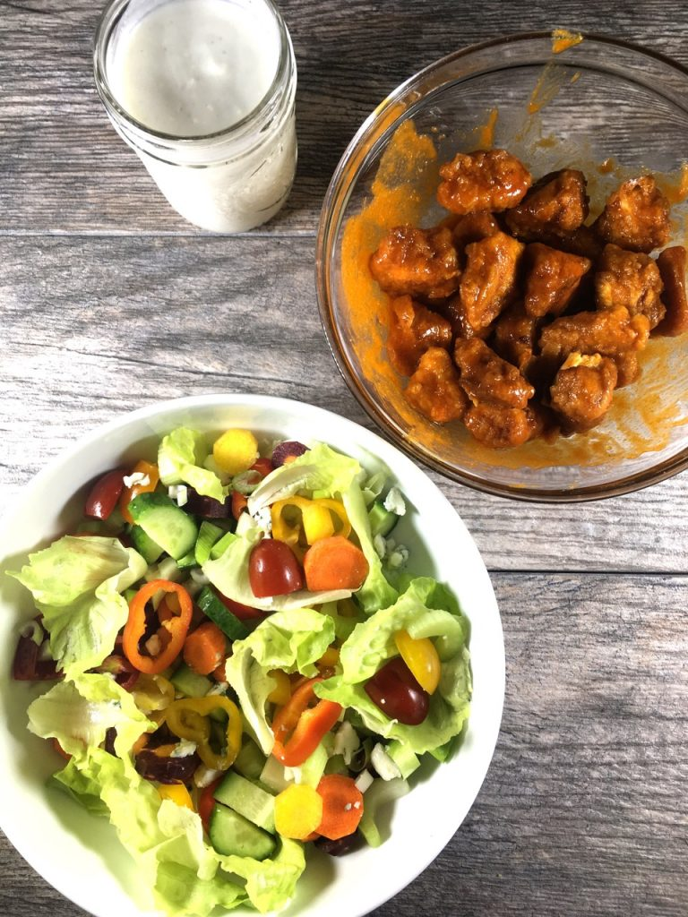 Gluten-Free Fried Chicken Tossed in Buffalo Sauce, Salad with veggies and blue cheese, and Goat Milk Blue Cheese Dressing