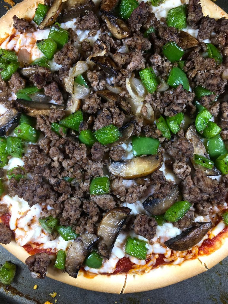 Philly Cheesesteak Pizza made with a Schär gluten-free pizza crust, ground bison, goat mozzarella cheese, organic pizza sauce, mushroom, bell peppers and shallots