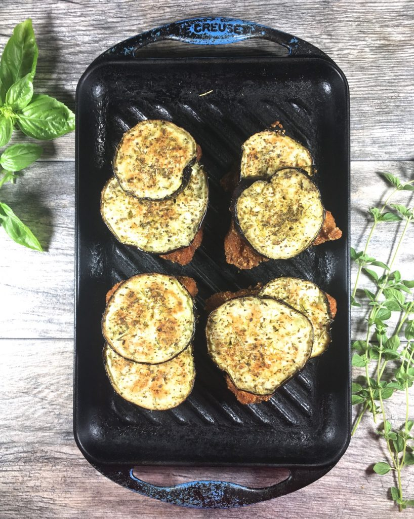 Italian seasoned eggplants on top of fried chicken for the eggplant chicken Parmesan.