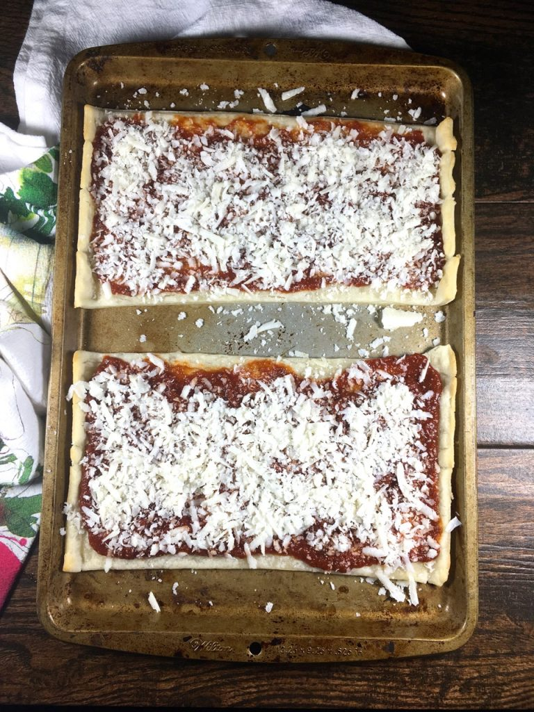 Schär gluten-free puff pastry crust cut in half on a baking sheet, cooked 6 minutes, covered with pizza sauce and goat mozzarella cheese