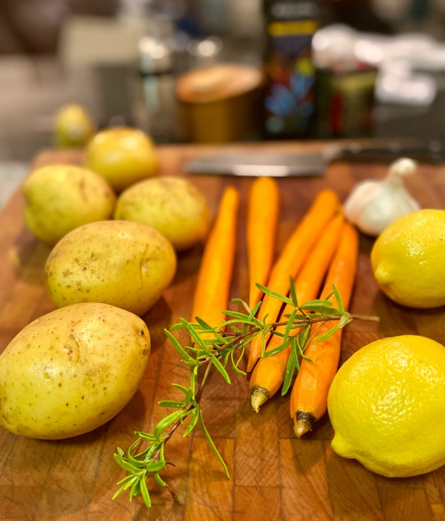 potatoes, carrots, lemons, garlic and fresh rosemary on a cutting board