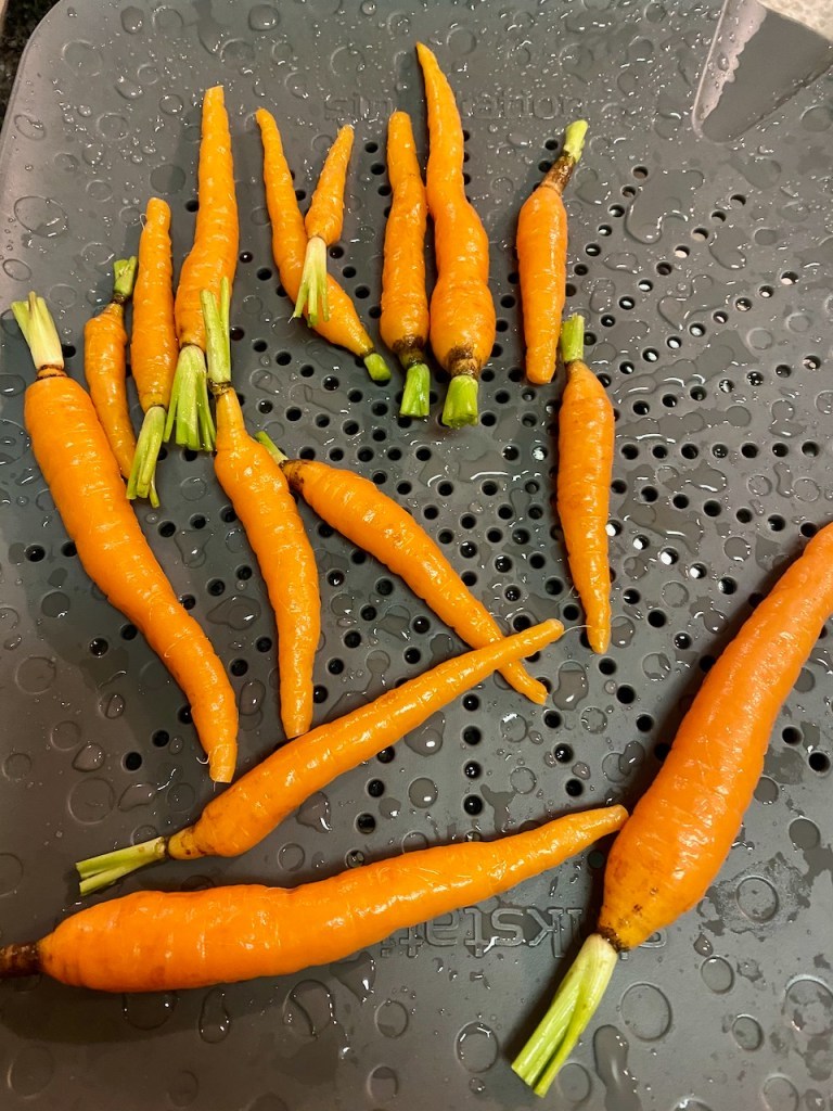 Small organic carrots scrubbed and rinsed with water, cooked in a skillet, and will be drizzled with Cayenne Date Nectar