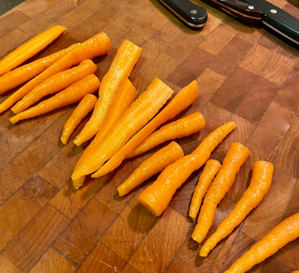 Cutting some of the thicker organic carrots in half on a cutting board