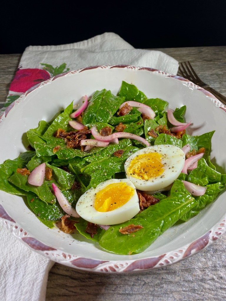 spinach salad with warm bacon dressing, marinated onions, bacon, and boiled eggs