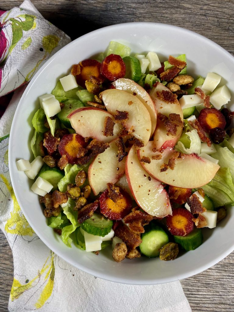 Summer salad with nectarines, pomegranate flavored pistachios nut mix, and summer peach balsamic vinegar.
