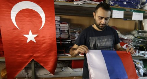 A local Turkish man sells Russian flags along Turkish flags. Russian flags have become a popular item for sale in Turkey.