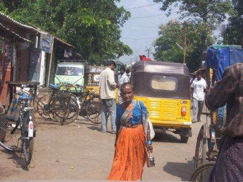 Old Hindi woman walking through  busy street in India