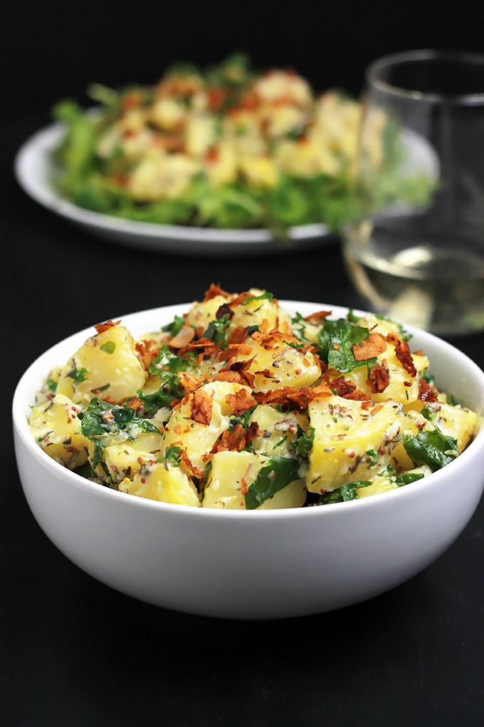 Vegan Yukon Kale Potato Salad in a bowl with the potato salad on a bed of arugula with coconut bacon on top in the background.