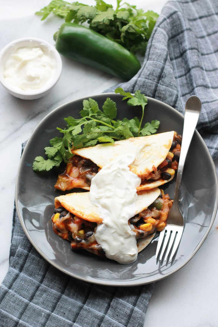 Baked Black Bean Tacos with Red Chile Sauce on plate with sour cream