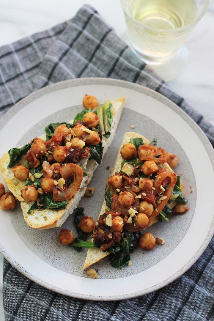 close-up shot of ciabatta garlic toast with spinach, chard and chickpeas on top, with a glass of wine in background.