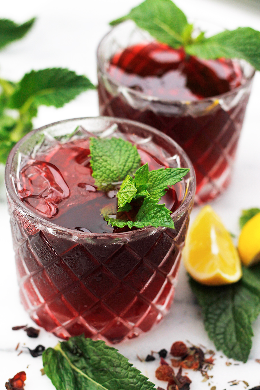 Close-up overhead shot of two glasses of Sweet Vermouth Hibiscus Tea Cocktail.