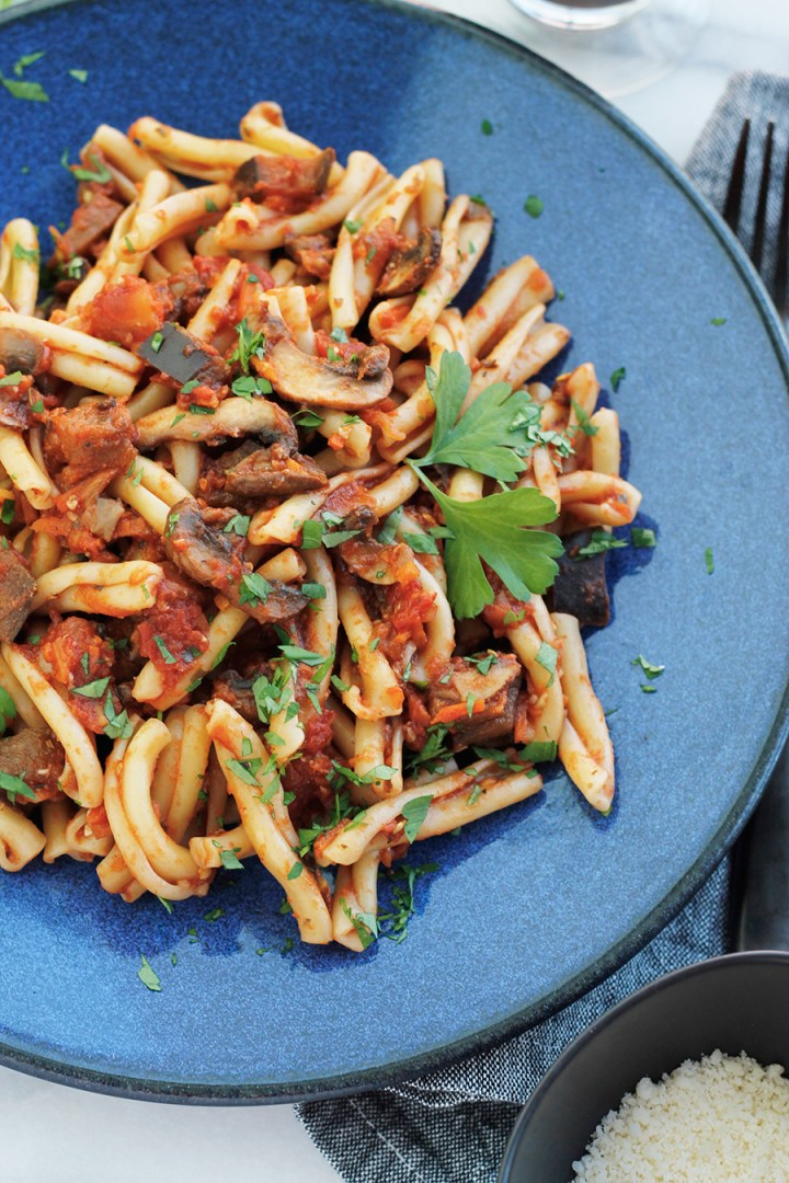 Blue plate filled with Vegan Eggplant Mushroom Bolognese Sauce tossed with Casarecce pasta.