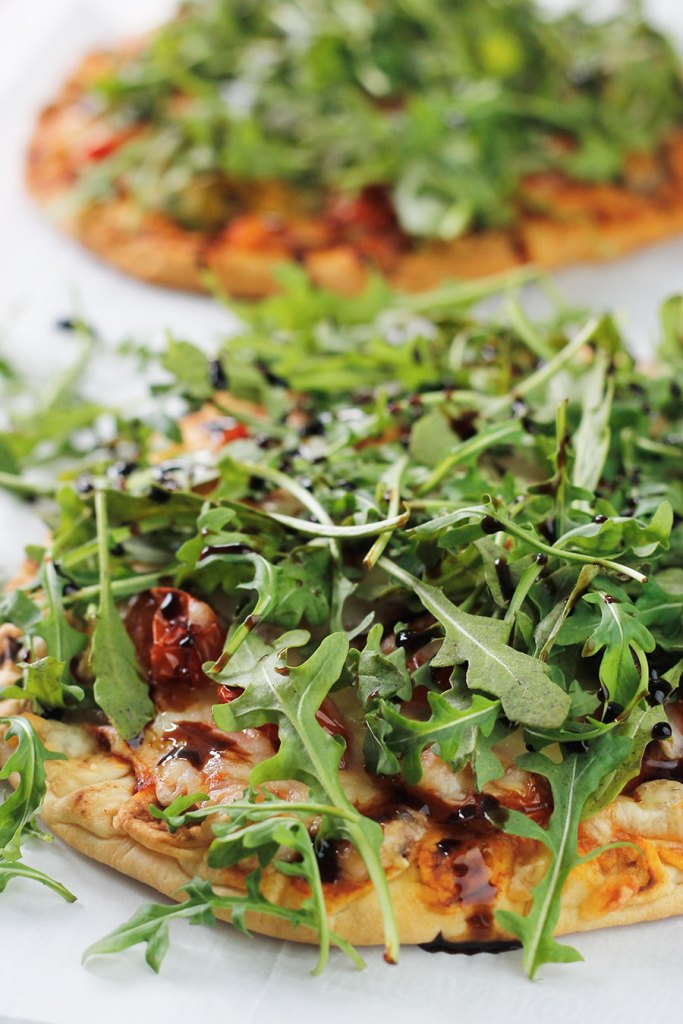 Two unsliced roasted veggie pizzas topped with arugula and drizzled with balsamic glaze.