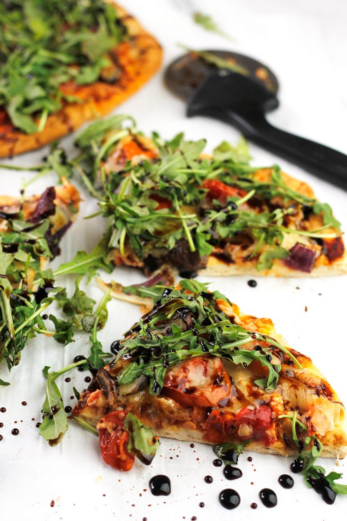 Slices of roasted veggie pizza topped with arugula and drizzled with balsamic glaze.